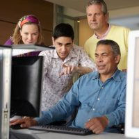 Adult students around a computer, Socialization and brain health